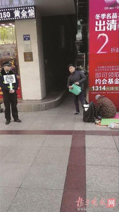 """城管在假乞丐旁举牌 这个""""乞丐""""很有故事曾去过新加坡乞讨"""
